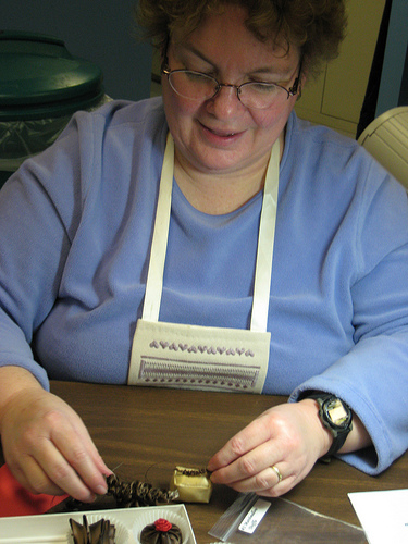 Susan A. puts finishing touches on her pieces